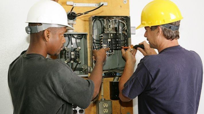 dois-profissionais-eletricistas-trabalhando-quadro